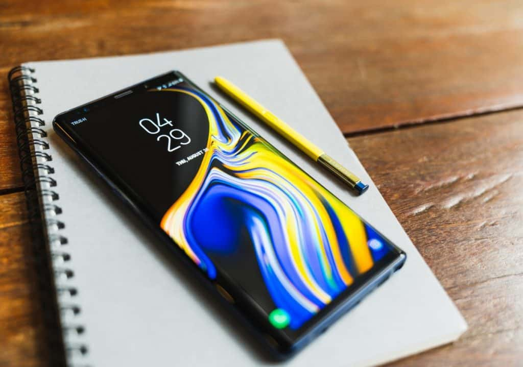Galaxy Note 9 with yellow S pen stylus on a notebook