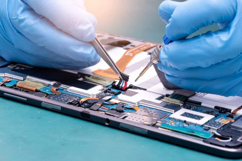 technician assembling inside of tablet by screwdriver in the lab