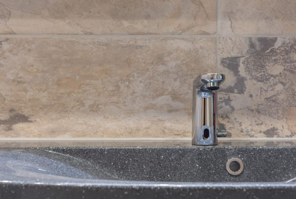 Sink in a bathroom with modern bathroom tap and tiles in natural stone look