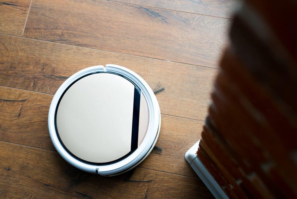 remote-controlled vacuum cleaner vacuums laminate flooring near a brick wall