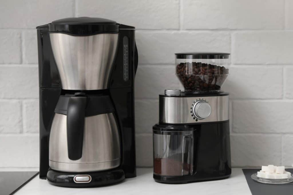 Modern coffee maker and grinder on counter in kitchen