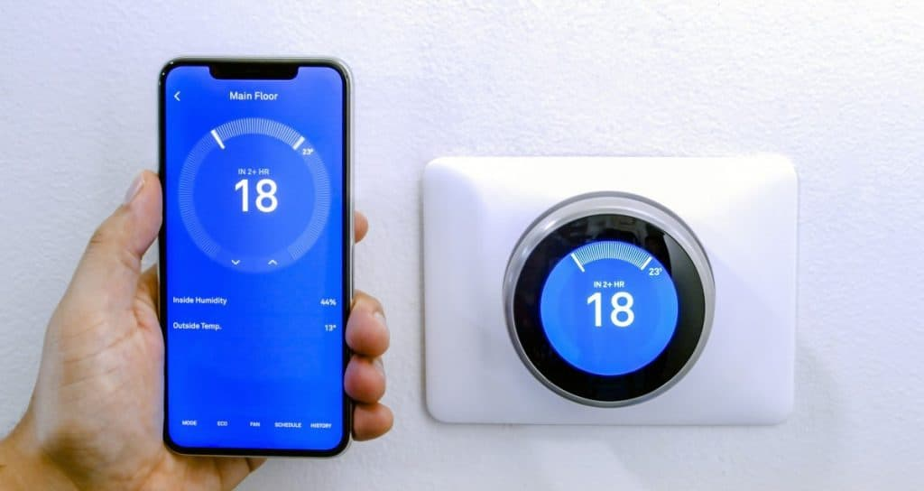 smart phone using a wireless Thermostat on a white wall