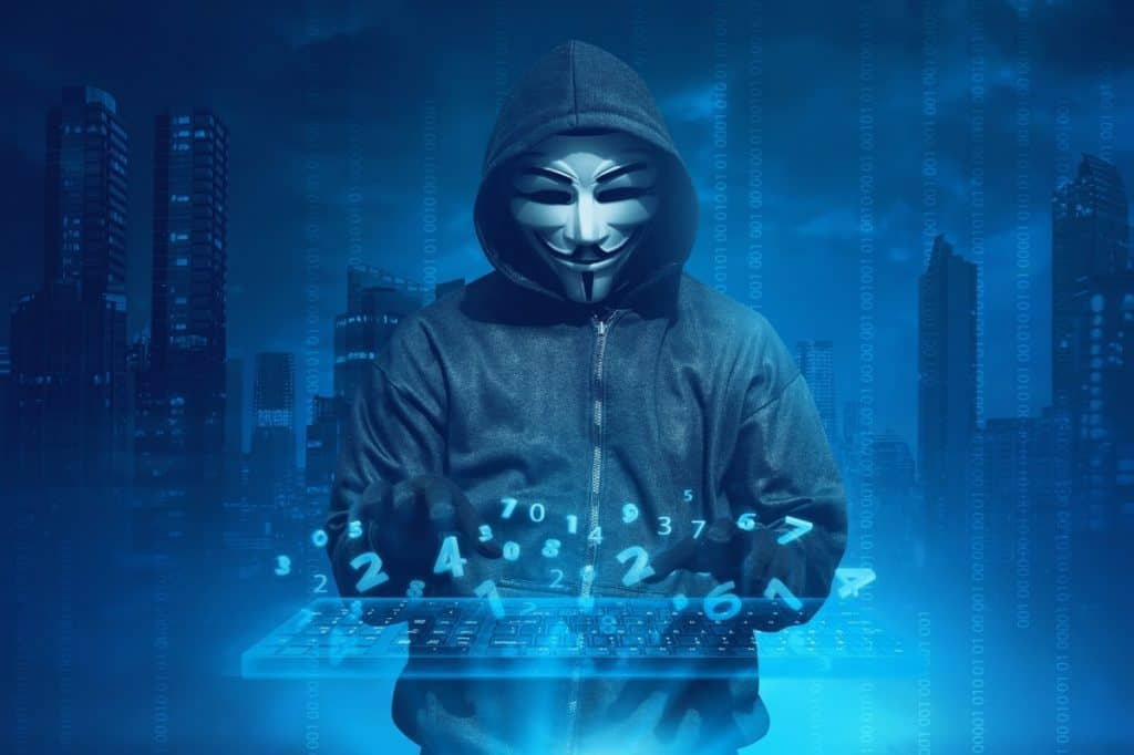 Hooded man with anonymous mask hacking system online security